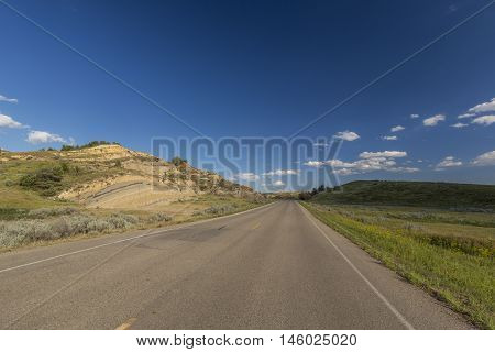 A road traveling through some badlands during summer.