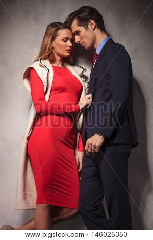 sexy elegant couple standing close to each other, woman pulling business man's suit in studio