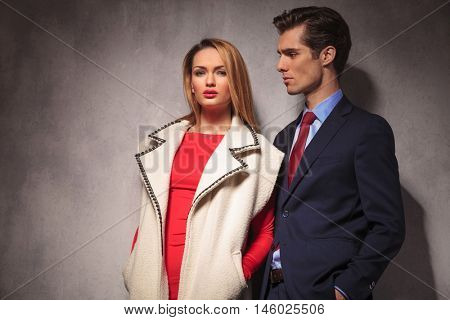 elegant couple posing together in studio, man in suit and tie, woman in red dress and long coat