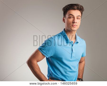 side view of a young casual man wearing blue polo shirt, standing with hands on waist and looks away from the camera, on grey studio background