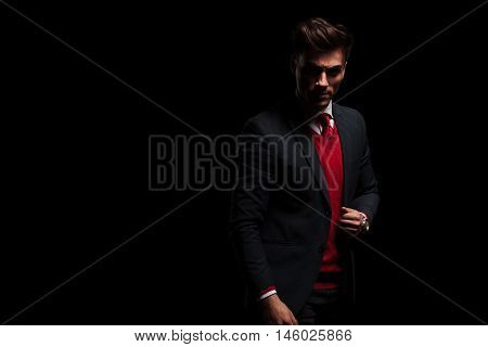 serious young business man standing on black background in studio