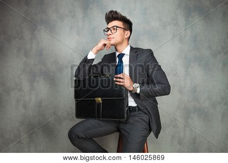 smiling young business man with glasses and holding briefcase is thinking and looks away from the camera