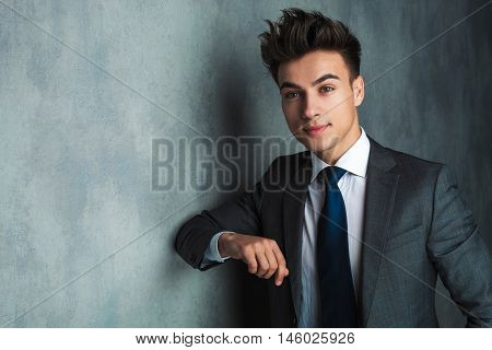 young businessman leaning his elbow against wall and looks away from the camera in studio