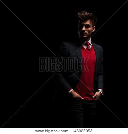 young businessman standing with hands in pockets and looks over his shoulder to a side on black background