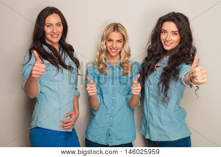 three happy women in jeans clothes making the ok thumbs up hand gesture in studio