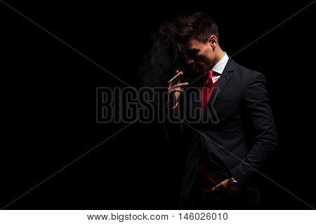 young business man is thinking while smoking his cigarette on black studio background