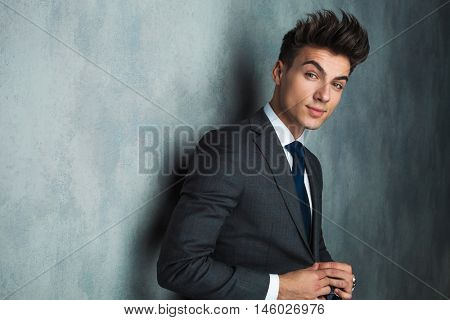 side view of a young businessman buttoning his suit and looks at the camera