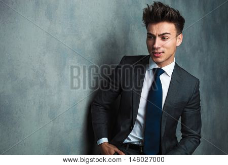 angry young businessman sitting and looking away from the camera in studio