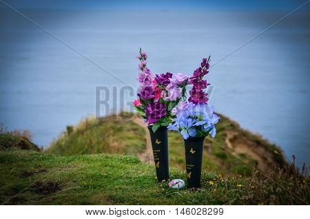 Flowers on the sea shore in remembrance scatter the ashes of deceased