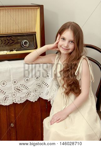 Gentle little girl with long brown hair to her waist . Girl sitting on an old Viennese chair near the old radio receiver