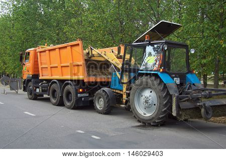 Smolensk, Russia - August 08, 2014: The tractor loads of fallen leaves from the roadside in the truck