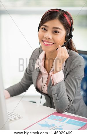 Portrait of lovely young Vietnamese helpdesk operator