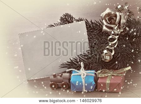 Vintage Christmas card wooden steam train toy gifts blank paper. Toned sepia