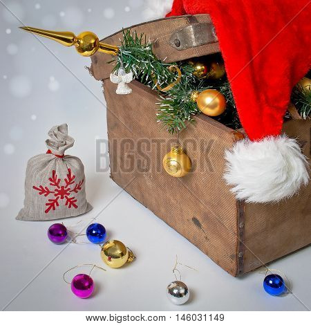 Old chest with a Christmas tree balls and red cap