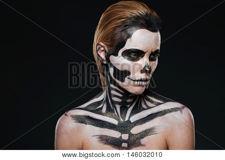 Portrait of woman with intimidating halloween makeup over black background