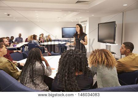 Female teacher addressing university students in a classroom
