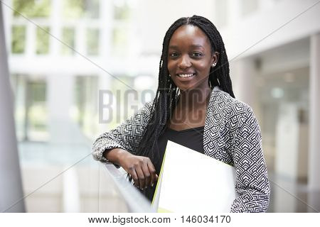 Smiling young black female student in university foyer
