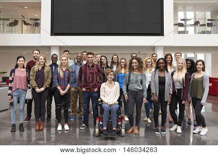 Student group standing in atrium under a big AV screen