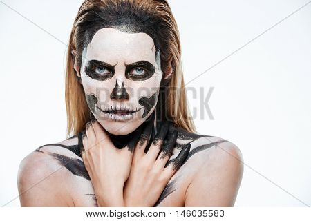 Portrait of girl with fearful skeleton makeup over white background