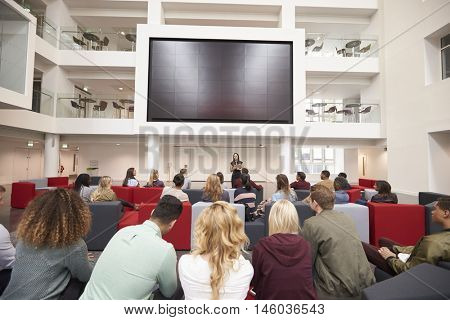 Back view of students at a lecture in a university atrium