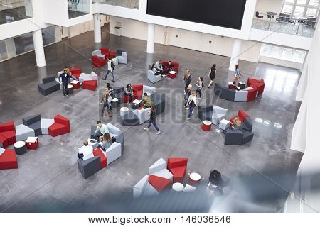 Busy university atrium area, seen from an indoor  balcony