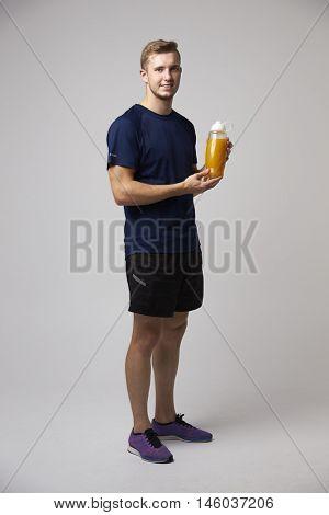 Studio Portrait Of Male Nutritionist With Drinks Bottle