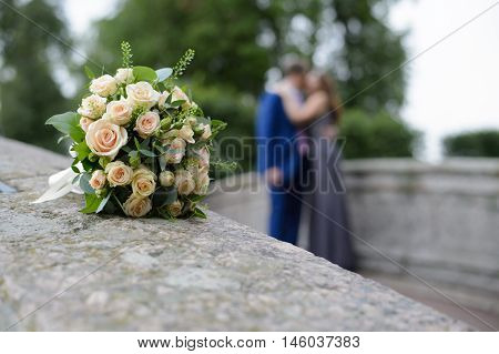 Couple in love and a bouquet of roses. Feelings of tenderness men and women. Romantic meeting of two loving adults.