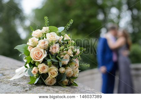 Couple in love and a bouquet of white roses. Feelings of tenderness men and women. Romantic meeting of two loving adults.
