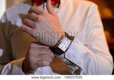 Guy wears the watch on your wrist. Fashionable gentleman getting dressed. Dressing elegant men at a festive reception.