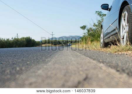 Car Parked By The Side Of A Road In Rural Country. Ambush By Black Car On A Asphalt Road. View Towar