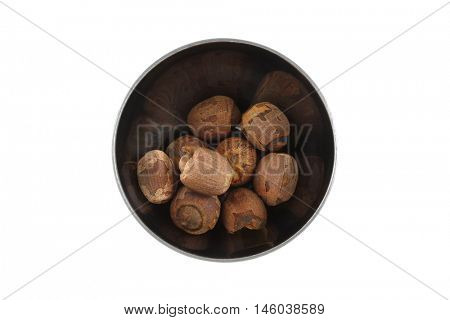 Top view of dried Lotus seeds in metal silver bowl. Dry lotus nuts isolated on white background.