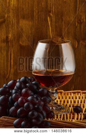 a glass of brandy and a bunch of grapes on a wicker table on the wooden background