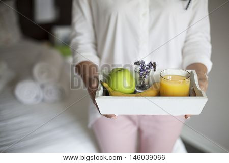 Maid with Tray with breakfast in a hotel room