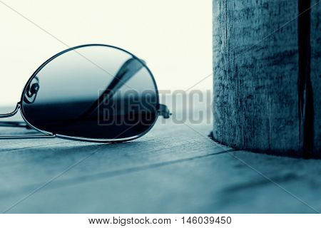 Mirrored Sunglasses Detail on the Wooden Background Close Up and Selective Focus. Fashion Concept in Cyan.