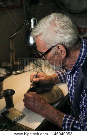 Senior Man Soldering Tin Plate In Workshop.