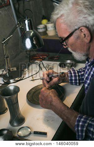 Senior man bending solder in a workshop.