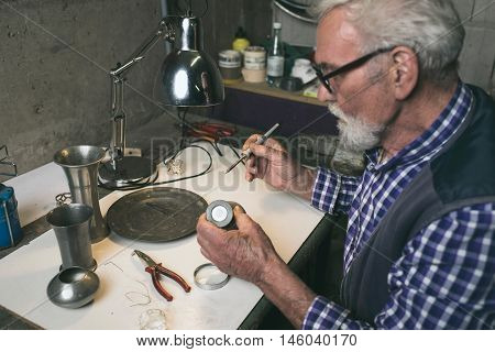 Senior man soldering an old tin vase