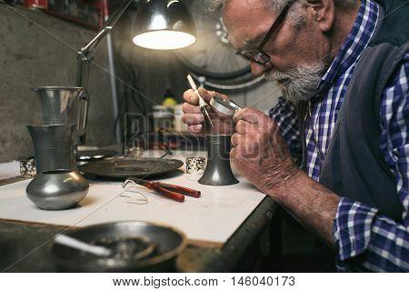 Senior man soldering an old tin vase