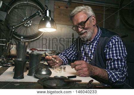 Smiling senior man soldering metal rings in workshop
