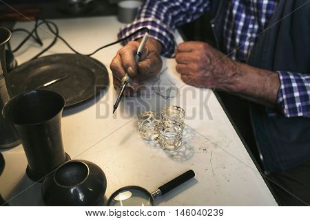 Hand Of Senior Man With Soldering Iron
