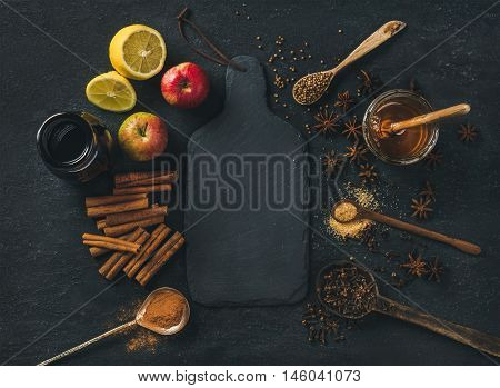Ingredients for making mulled wine. Wine in glass bottle, honey, lemon, apples and spices over black slate stone background with board in center, top view, copy space