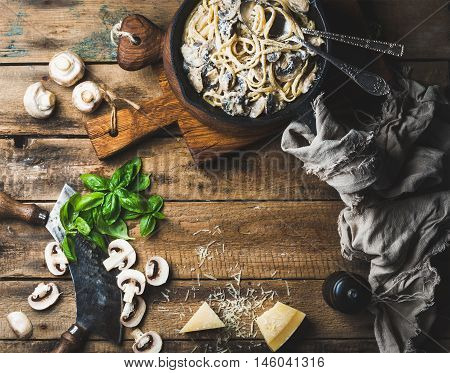 Italian style dinner with copy space. Creamy mushroom pasta spaghetti in cast iron pan with Parmesan cheese, fresh basil and pepper over old rustic wooden background. Top view, horizontal composition