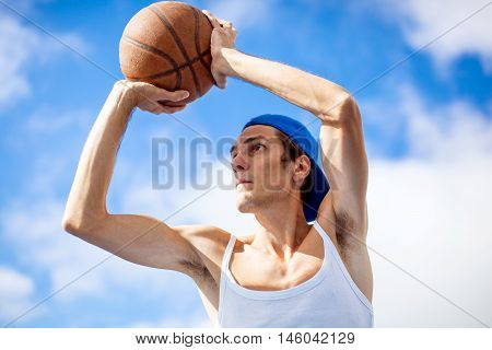 Young guy is playing basketball. He is preparing to throw the ball in the basket