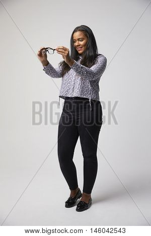 Studio Portrait Of Female Optician Looking At Spectacles