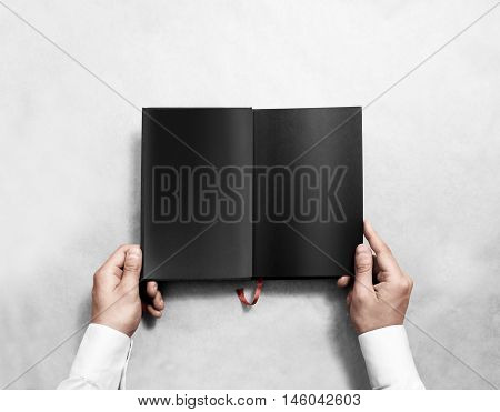 Hand holding blank opened book mock up with black pages. Person reading empty paperback mockup. Black notebook inside template. Publication design leafing man. Textbook spread with bookmark.