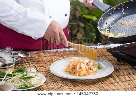 Chef putting Pad Thai to the plate / cooking Pad Thai concept