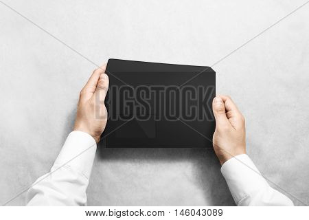 Black blank envelope mock up holding in hand. Empty letter with transparent window design mockup. Message template presentation. Person opening clear mail.