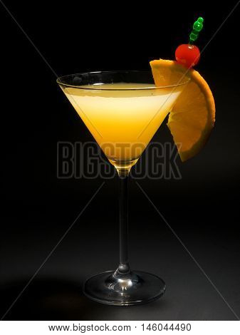 Cocktail Bronx with gin vermouth and orange juice. Isolated on black background. Full length