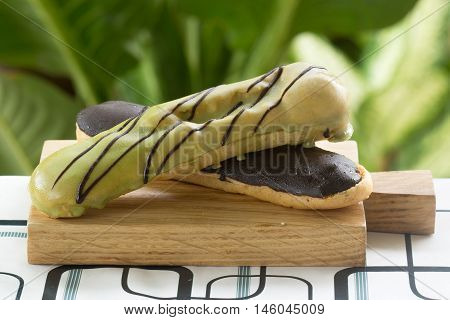 Green Tea and chocolate coating Eclair on the wooden plate