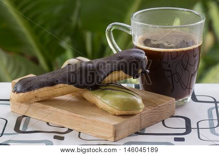 Green Tea and chocolate coating Eclair and black coffee